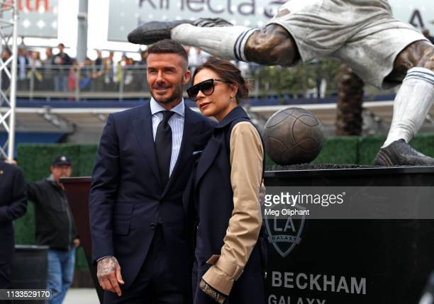 David Beckham and his wife Victoria Beckham pose for a photo with his statue at Dignity Health Sports Park on March 02, 2019 in Carson, California.