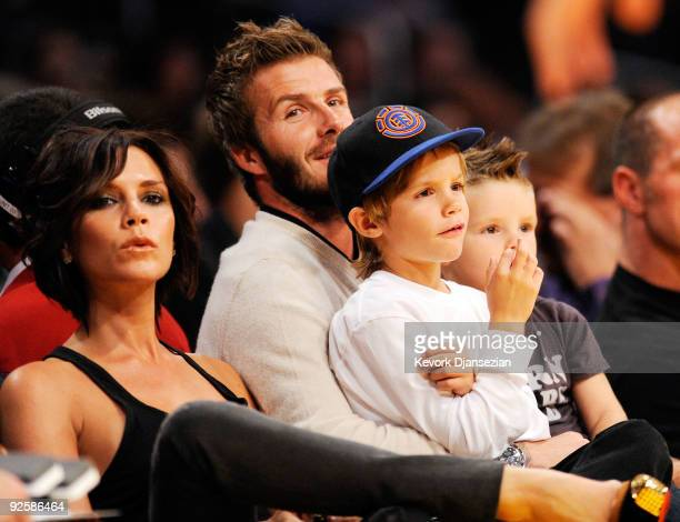 David Beckham and his wife Victoria follow the action between the Los Angeles Lakers and the Dallas Mavericks along with their children Cruz left and...
