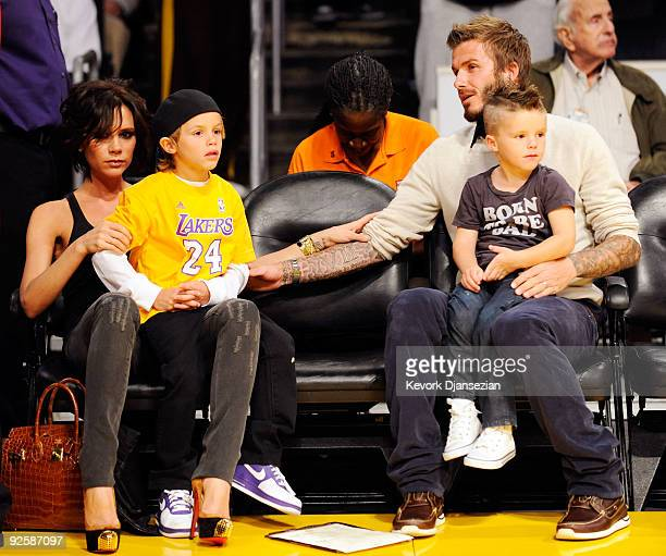 David Beckham and his wife Victoria follow the action between the Los Angeles Lakers and the Dallas Mavericks along with their children Cruz and...
