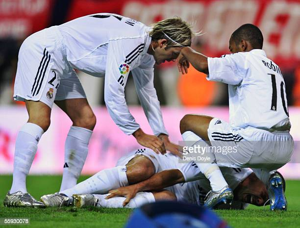 David Beckham and Robinho comfort a fallen Ronaldo of Real Madrid after he was injured while scoring his third goal against Atletico during a La Liga...