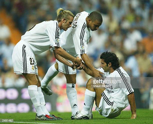 David Beckham and Ronaldo of Real Madrid help teammate Luis Figo to his feet during the Spanish Primera Liga match between Real Madrid and Valladolid...