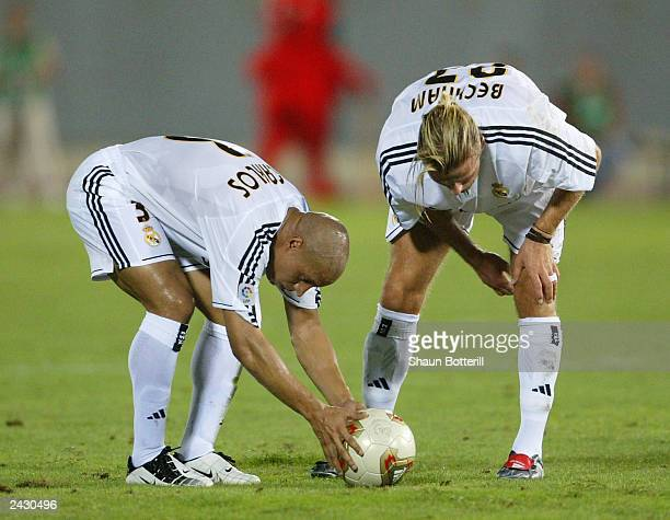 David Beckham and teammate Roberto Carlos of Real Madrid both prepare for a freekick during the Spanish Super Cup Ist leg match between Real Mallorca...