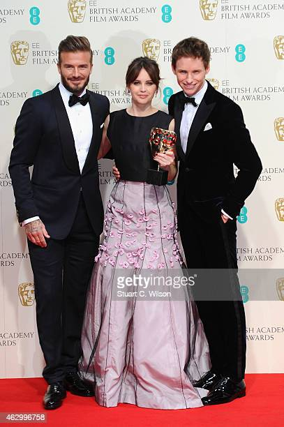 David Beckham Felicity Jones and Eddie Redmayne pose in the winners room at the EE British Academy Film Awards at The Royal Opera House on February 8...