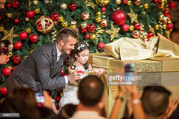 David Beckham helps a young girl turn the handle on a jackinthebox at the Festive Light up Event at The Shoppes at Marina Bay Sands on November 15...
