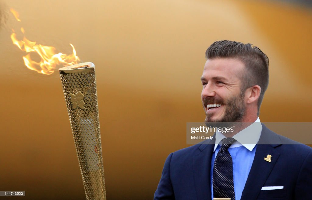 David Beckham holds the Olympic Flame as it arrives at RNAS Culdrose near Helston on May 18, 2012 in Cornwall, England. The Olympic Flame arrived in the UK after it was handed over at a ceremony yesterday in Athens. A British delegation including David Beckham, flew back with the flame from Greece where they attended a ceremony welcoming the flame, before it is taken on a 70-day relay involving 8,000 torchbearers covering 8,000 miles.