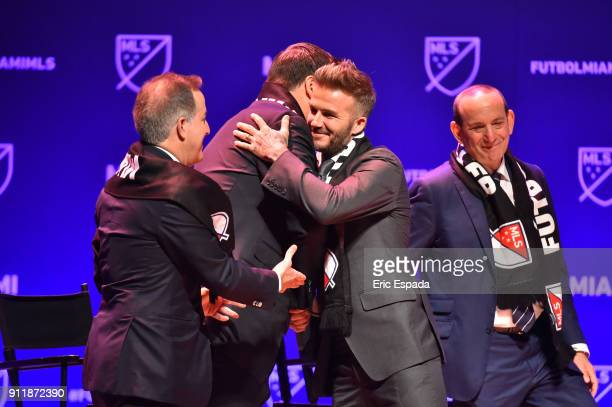 David Beckham hugs Sprint CEO Marcelo Clarue during the press conference announcing an MLS franchise in Miami at the Knight Concert Hall on January...