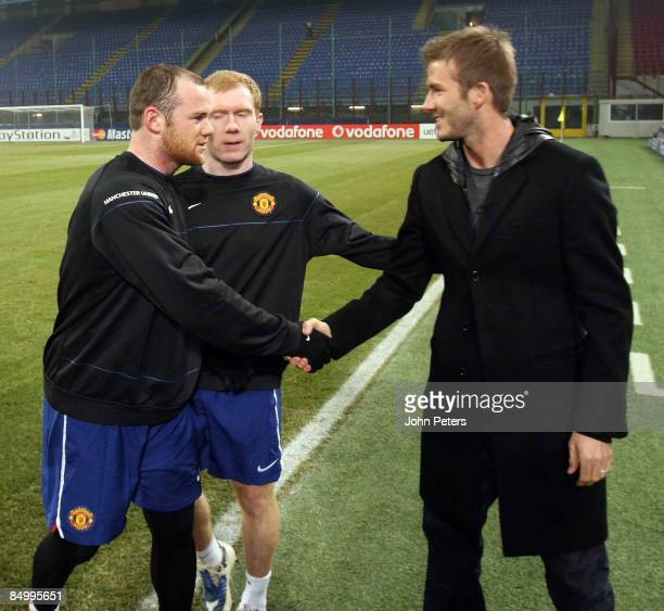 David Beckham of AC MIlan speaks with Paul Scholes and Wayne Rooney of Manchester United during a training session ahead of their UEFA Champions...