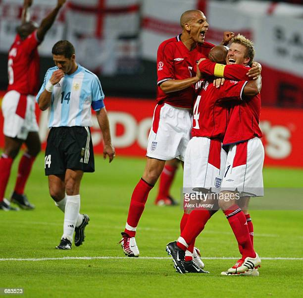 David Beckham of England celebrates with team mates Rio Ferdinand and Trevor Sinclair after winning the England v Argentina Group F World Cup Group...