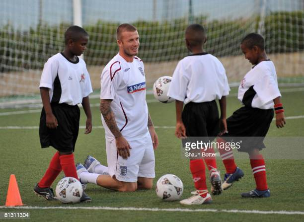 David Beckham of England interacts with kids during a coaching clinic for local children at the Marvin Lee Stadium on May 30 2008 in Port of Spain...