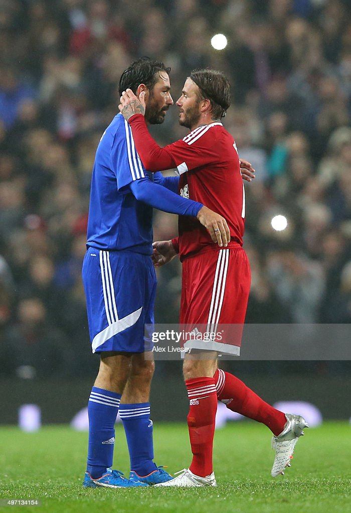 David Beckham (R) of Great Britain and Ireland hugs Robert Pires (L) of the Rest of the World as he is substituted in the second half during the David Beckham Match for Children in aid of UNICEF between Great Britain & Ireland and Rest of the World at Old Trafford on November 14, 2015 in Manchester, England.