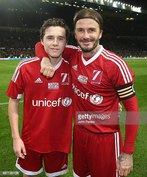 David Beckham of Great Britain and Ireland poses with his son Brooklyn Beckham after the David Beckham Match for Children in aid of UNICEF between...