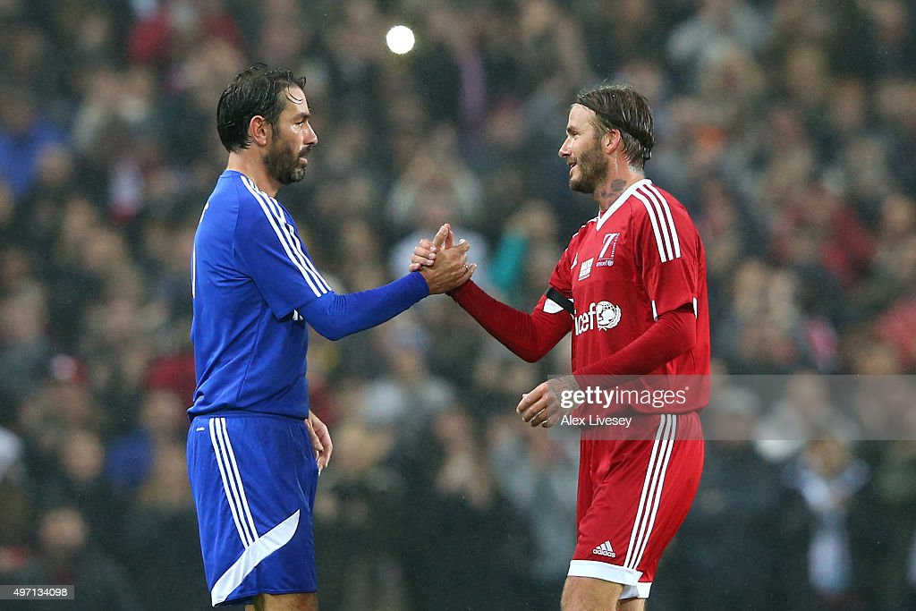 David Beckham (R) of Great Britain and Ireland shakes hands with Robert Pires (L) of the Rest of the World as he is substituted in the second half during the David Beckham Match for Children in aid of UNICEF between Great Britain & Ireland and Rest of the World at Old Trafford on November 14, 2015 in Manchester, England.
