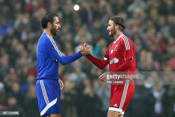 David Beckham of Great Britain and Ireland shakes hands with Robert Pires of the Rest of the World as he is substituted in the second half during the...