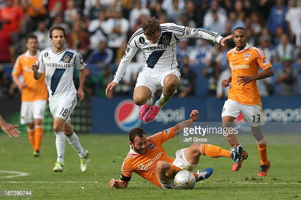 David Beckham of Los Angeles Galaxy leaps over Brad Davis of Houston Dynamo in the second half in the 2012 MLS Cup at The Home Depot Center on...