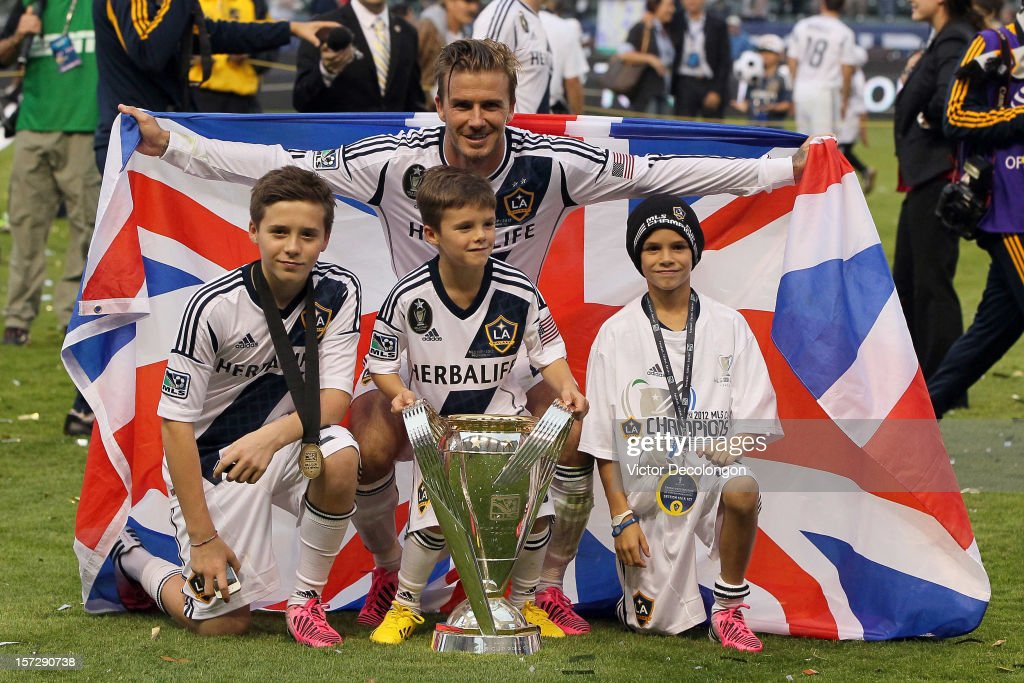 David Beckham #23 of Los Angeles Galaxy poses with his sons Brooklyn Beckham, Cruz Beckham and Romeo Beckham after the Galaxy defeat the Houston Dynamo 3-1 to win the 2012 MLS Cup at The Home Depot Center on December 1, 2012 in Carson, California.