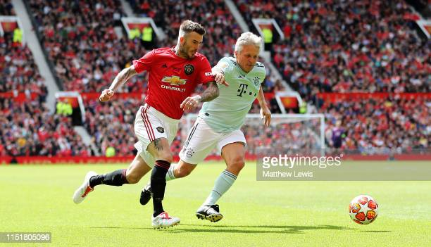 David Beckham of Manchester United '99 Legends beats Andreas Ottl of FC Bayern Legends during the Manchester United '99 Legends and FC Bayern Legends...
