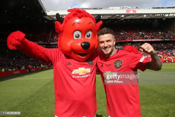 David Beckham of Manchester United '99 Legends celebrates with Fred the Red at the end of the 20 Years Treble Reunion match between Manchester United...