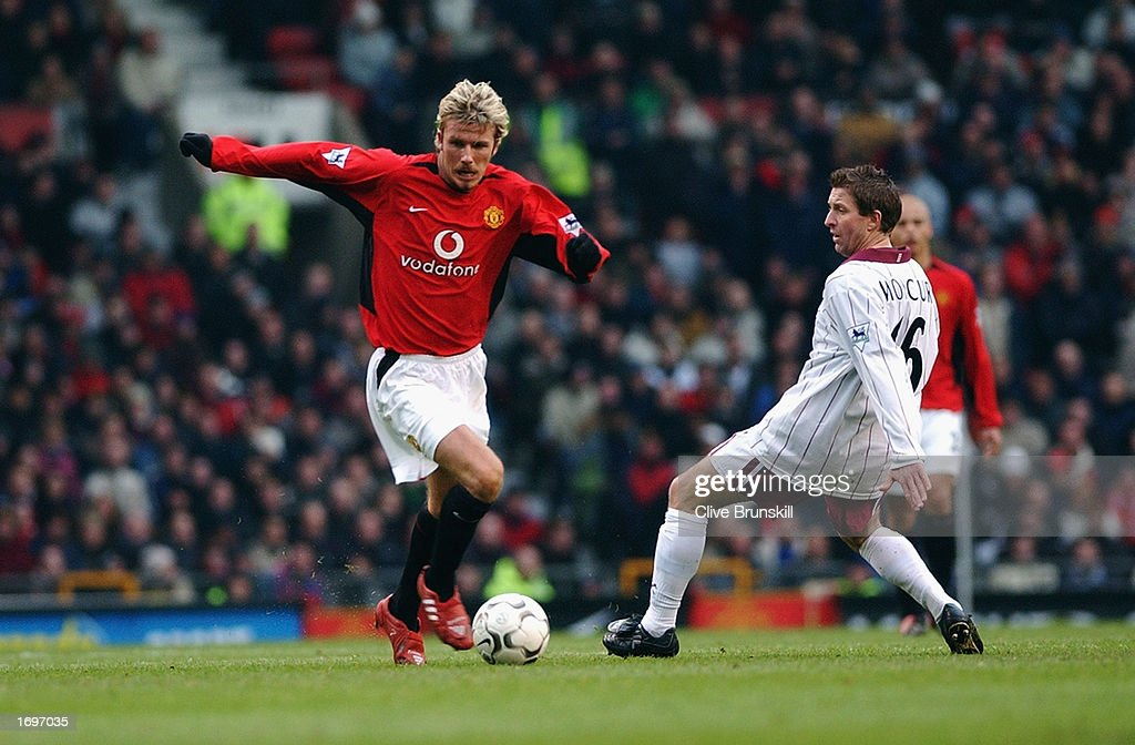 David Beckham of Manchester United skips past a challenge from John Moncur of West Ham United : News Photo