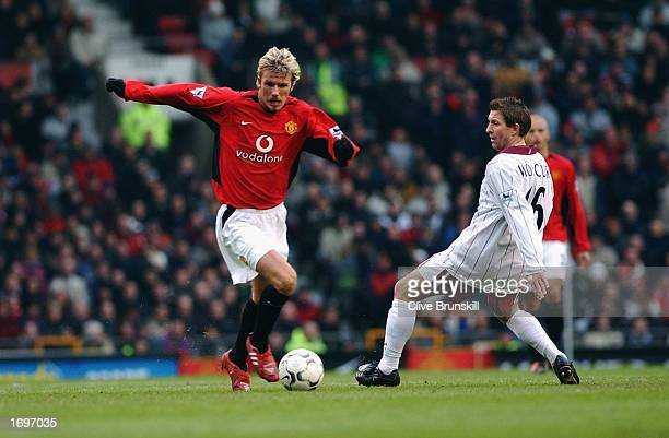 David Beckham of Manchester United skips past a challenge from John Moncur of West Ham United during the FA Barclaycard Premiership match between...