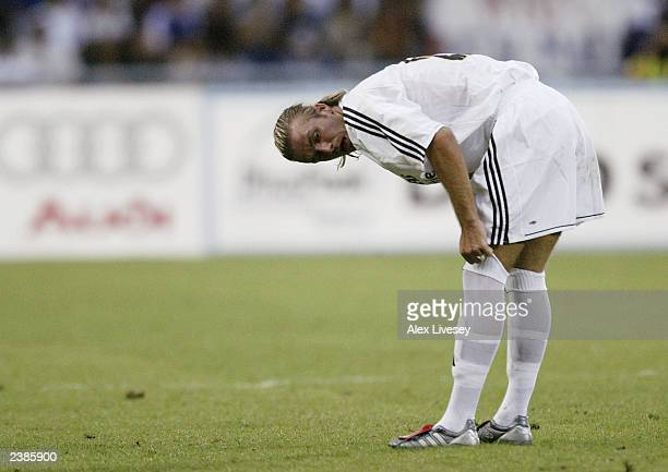 David Beckham of Real Madrid adjusts his socks during the pre season friendly match between Thailand and Real Madrid at the Rajamangala Stadium on...