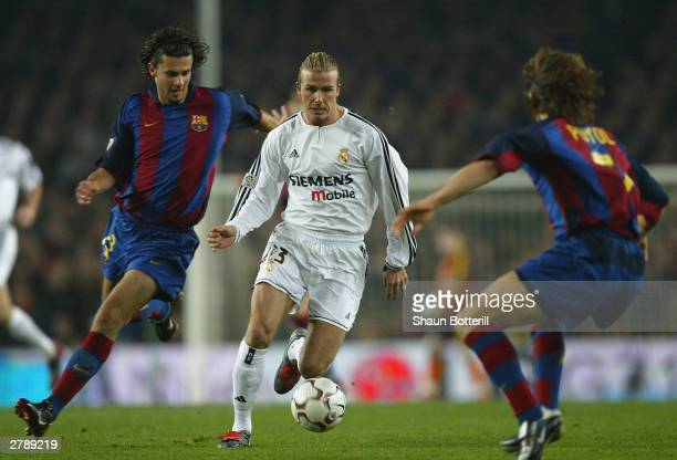 David Beckham of Real Madrid is challenged by Motta and Puyol of Barcelona during the Spanish Primera Liga match between Barcelona and Real Madrid at...