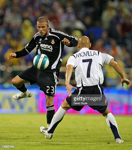 David Beckham of Real Madrid is tackled by Movilla in the Primera Liga match between Real Zaragoza and Real Madrid at the Romareda stadium on June 9,...