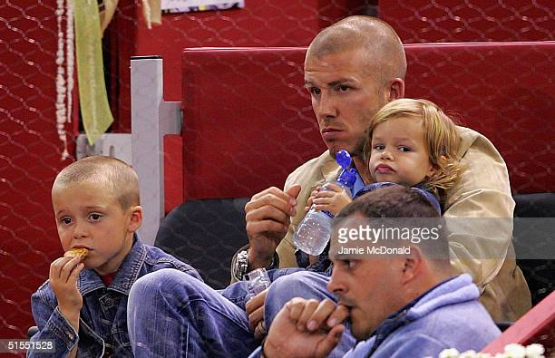 David Beckham of Real Madrid with his children Romeo and Brooklin enjoy the moment during the Tommy Robredo v Andre Agassi quarter final match at the...