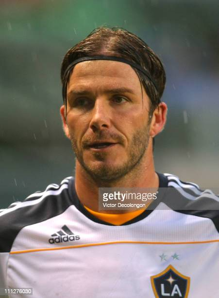 David Beckham of the Los Angeles Galaxy acknowledges Galaxy looks on prior to taking a corner kick during their MLS match against the New England...