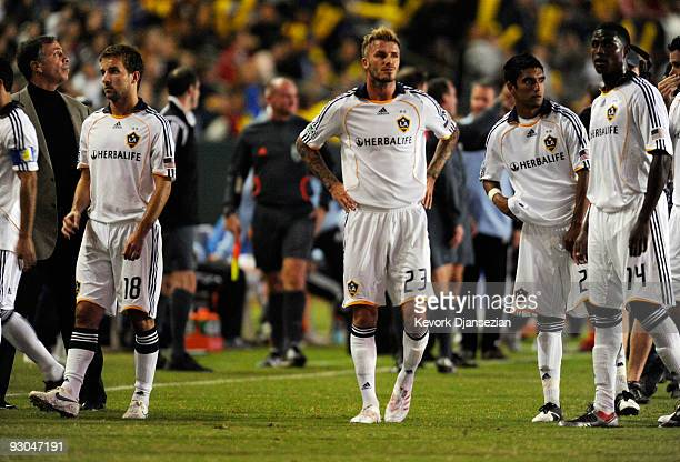 David Beckham of the Los Angeles Galaxy and his teammates wait for the stadium lights to come back on after a power outage in the first half during...