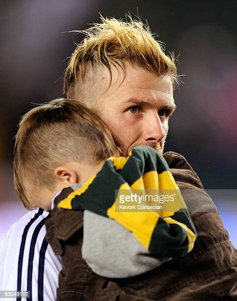 David Beckham of the Los Angeles Galaxy carries his son Cruz in his arms into the locker room after the Galaxy defeated the Houston Dynamo 20 in the...