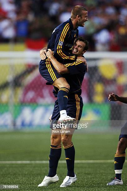 David Beckham of the Los Angeles Galaxy celebrates with Ian Russell after setting up Carlos Pavon for their second goal of the game against the New...