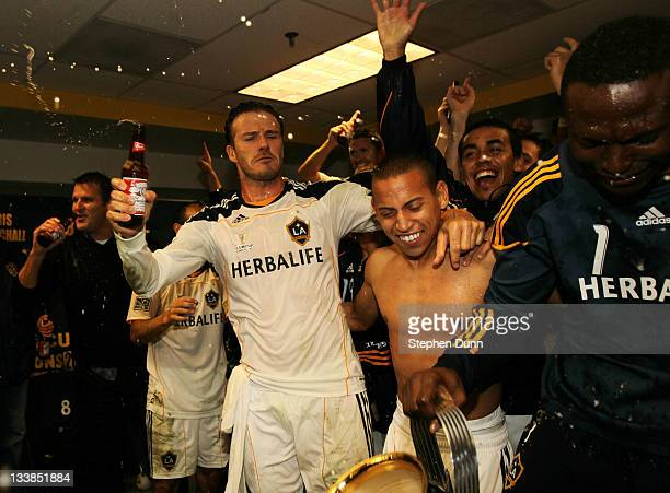 David Beckham of the Los Angeles Galaxy celebrates with Paolo Cardozo in the locker room after defeating the Houston Dynamo 10 in the 2011 MLS Cup at...