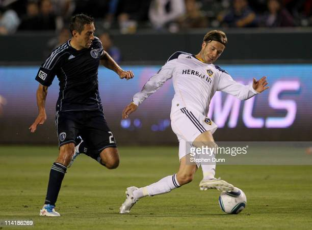 David Beckham of the Los Angeles Galaxy controls the ball in front of Davy Arnaud of Sporting Kansas City at The Home Depot Center on May 14 2011 in...