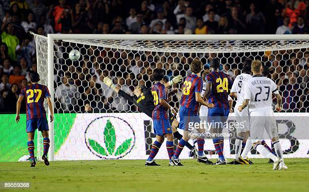 David Beckham of the Los Angeles Galaxy hits a free kick to score a goal against goalkeeper Jose Mauel Pinto of FC Barcelona during the first half of...