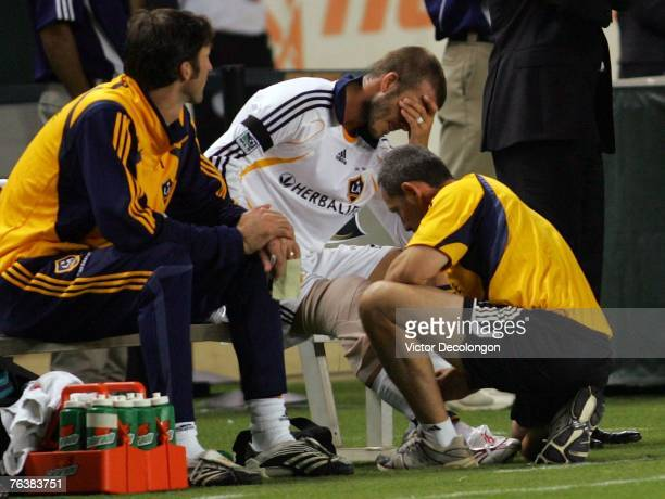 David Beckham of the Los Angeles Galaxy holds his head while a trainer wraps a bag of ice on his right knee after leaving the game against Pachuca...