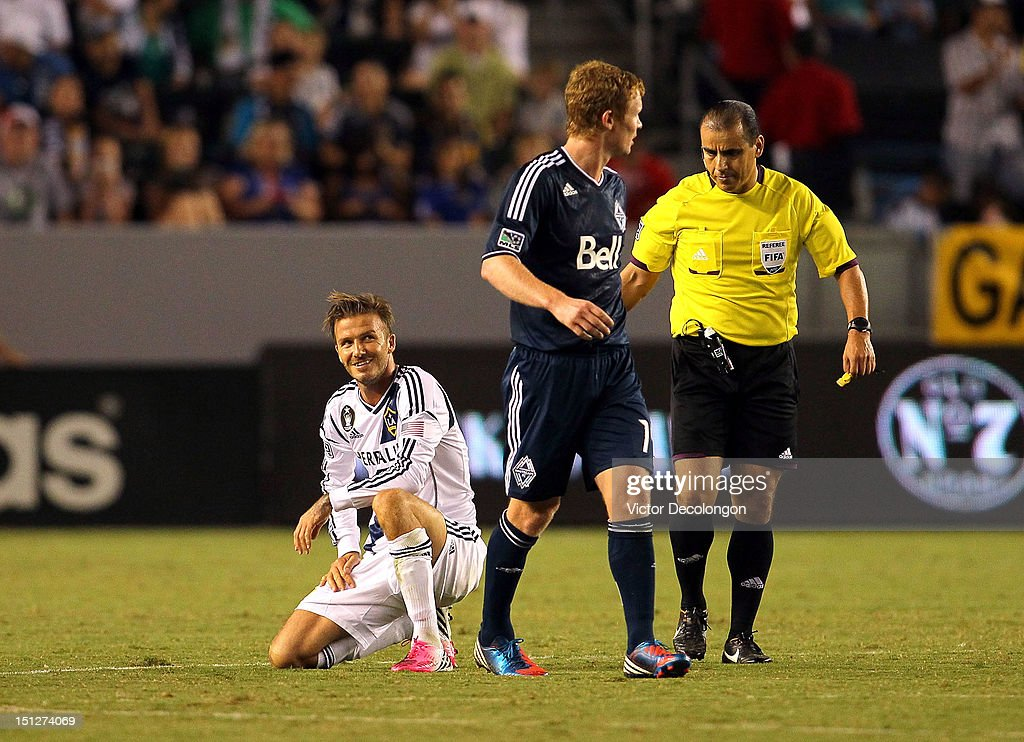 David Beckham #23 of the Los Angeles Galaxy smiles after being fouled as referee Baldomero Toledo and Barry Robson #14 of the Vancouver Whitecaps look on during the MLS match at The Home Depot Center on September 1, 2012 in Carson, California. The Galaxy defeated the Whitecaps 2-0.