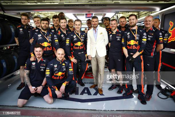 David Beckham poses for a photo with the Red Bull Racing team in the garage before the F1 Grand Prix of Bahrain at Bahrain International Circuit on...