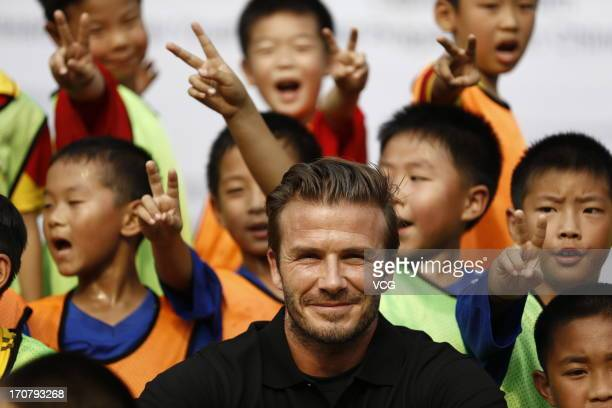 David Beckham poses for a photograph with young fans at Nanjing Olympic Sports Center on June 18, 2013 in Nanjing, China.