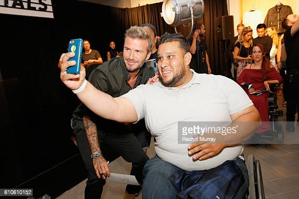David Beckham poses for photos with fans during the launch of David Beckham's H&M Modern Essentials Collection on September 26, 2016 in H&M at...