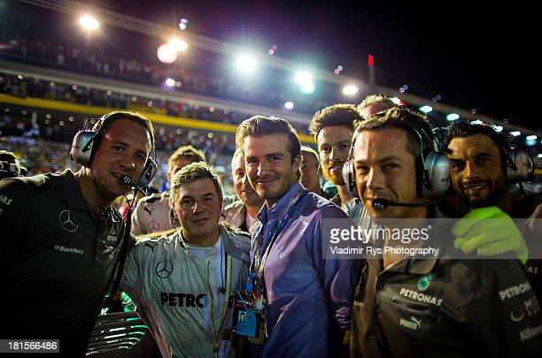David Beckham poses on the grid with Mercedes GP mechanics prior to the Singapore Formula One Grand Prix at Marina Bay Street Circuit on September...