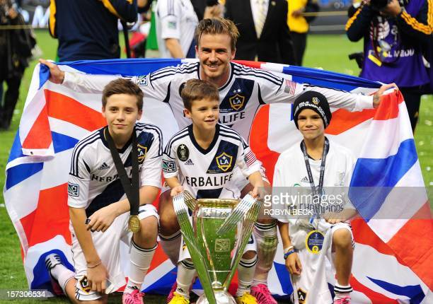 David Beckham poses with his sons Brooklyn Cruz and Romeo and the MLS Trophy after the Los Angeles Galaxy beat Houston Dynamo 31 in the Major League...