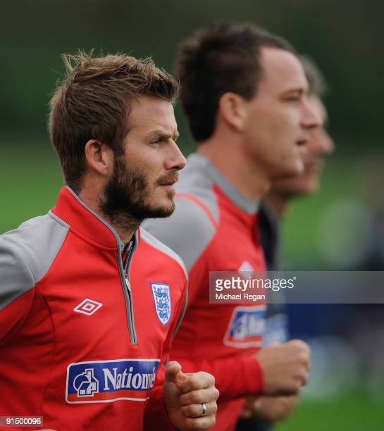 David Beckham runs with John Terry during the England training session at London Colney on October 6, 2009 in St Albans, England.