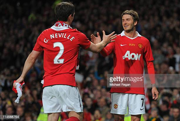 David Beckham shakes hands with Gary Neville after the Gary Neville Testimonial Match between Manchester United and Juventus at Old Trafford on May...