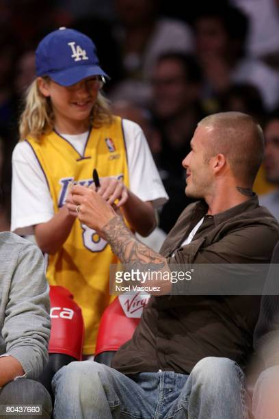 David Beckham signs an autograph for a fan at the Los Angeles Lakers vs Washington Wizards game at the Staples Center on March 30 2008 in Los Angeles...