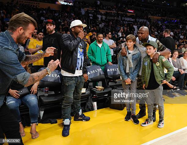 David Beckham takes a picture of Romeo Beckham Cruz Beckham and Floyd Mayweather Jr at a basketball game between the Boston Celtics and the Los...