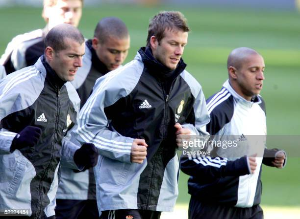 David Beckham warms up with teammates Zinedine Zidane and Roberto Carlos during a Real Madrid training session at the Santiago Bernabeu on February...