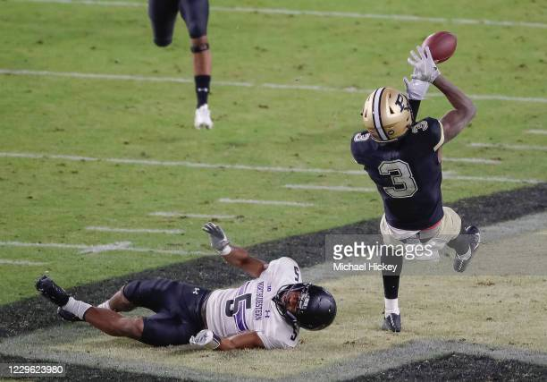 David Bell of the Purdue Boilermakers falls back to attempt to catch the ball as JR Pace of the Northwestern Wildcats falls to the ground during the...