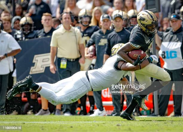 David Bell of the Purdue Boilermakers runs the ball as Caleb Peart of the Vanderbilt Commodores hangs on for the tackle during the first half at...