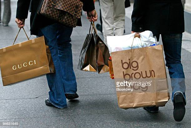David Benjamin left carries shopping bags including a Gucci bagand Paolo Presta right also carries shopping bags including a 'big brown bag' from...