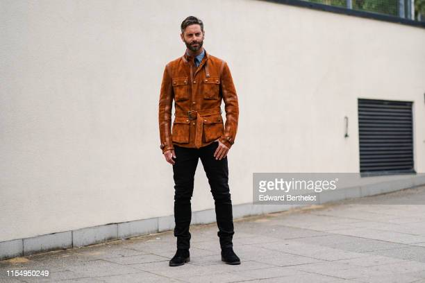 David Blakeley wears a brown/orange suede jacket black pants a blue shirt during London Fashion Week Men's June 2019 on June 09 2019 in London England